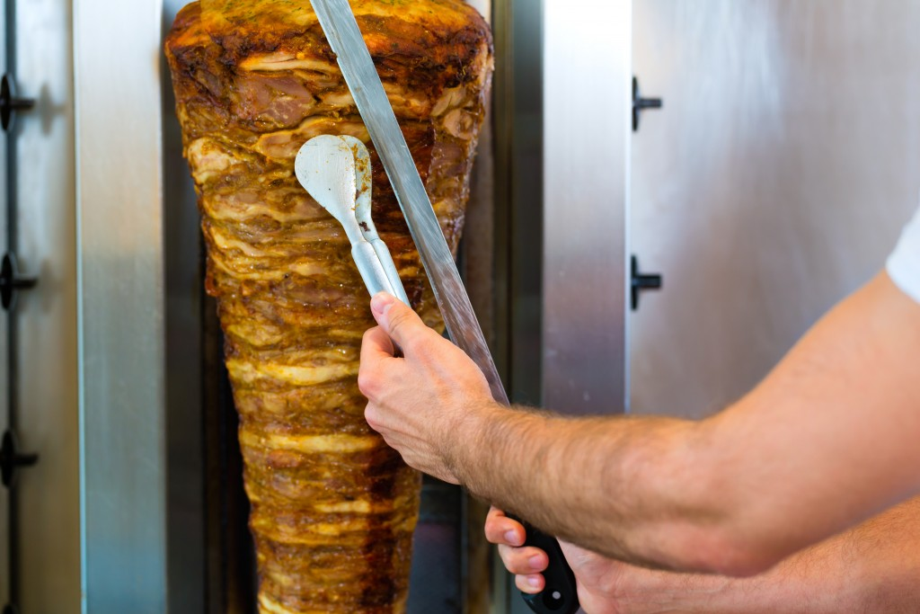 Doner kebab - friendly vendor in a Turkish fast food eatery, cutting meat with sharp knife in front of skewer